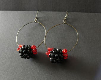 Hoop earrings with large black beaded bead accented by smaller red beaded beads