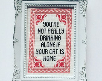 You're not really drinking alone if your cat is home. Finished and framed cross stitch.