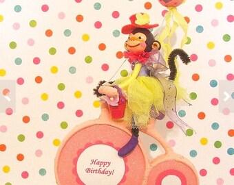 Bike Riding Girl Monkey in Purple, Pink, Yellow Cake Topper