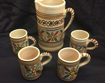 Sanguine pottery pitcher and mugs