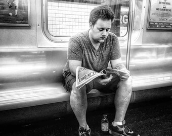 Man reading a newspaper on the subway