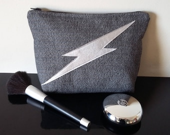 Grey cosmetic bag with silver lightening bolt