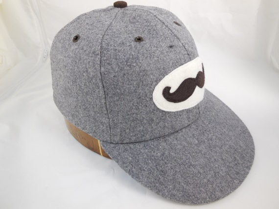 Felt Mustache Logo on a 6 panel dark grey wool  cap. Fitted with leather sweatband any size.