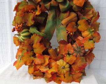 Oval pumpkin and squash wreath: faux-silk-artificial maple leaves; fall-autumn grapevine wreath; pumpkins and squash.