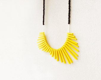 geometrical tribal necklace with yellow sticks and black beads, contemporary jewelry