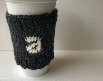 A monogrammed coffee cup cozy - knitted mug cozy