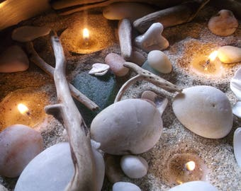 Candle sand, pebbles, driftwood and sea glass