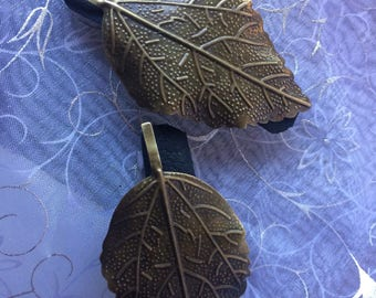 Gold colored metal leaf on black leather french barrette