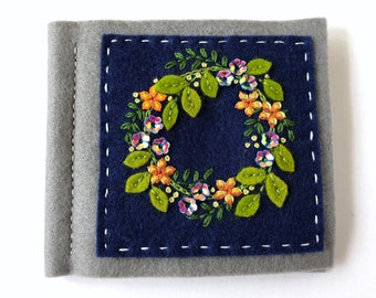 gray and blue hand embroidered needle book with sequins