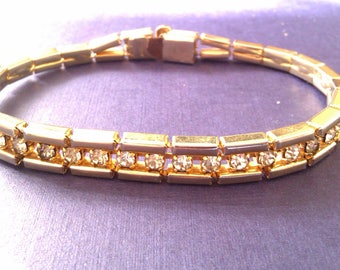gold coloured bracelet with clear stones