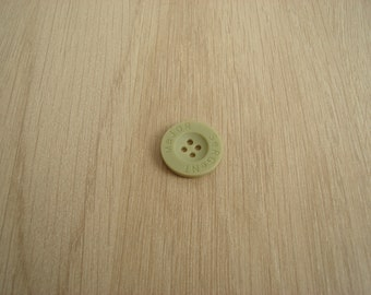 pale green button with flat edge and inscription