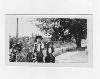 original 1949 black and white photo. two young boys in their cowboy outfit's