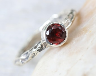 Tiny round faceted garnet ring in silver bezel setting with sterling silver hard textured oxidized band