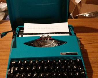 1977 teal Smith Corona Super G ultra portable typewriter with case lid