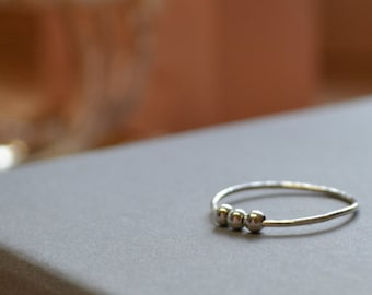 Delicate sterling silver stacking fidget ring, finely textured with moving sterling silver beads. Choose how many beads on yours.