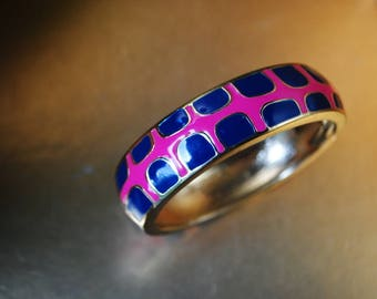Mod vintage 80s gold tone metal bangle bracelet with a pink  and navy blue geometric design. Made by Fornash.Size 7.
