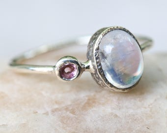 Oval cabochon moonstone ring with tiny pink tourmaline on the side in silver bezel setting with sterling silver high polished band