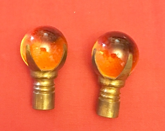 Two amber marble and brass lamp finials.