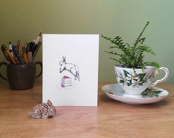 Cheerful greeting card features a white rabbit leaping over a cake. Available with birthday, congratulations, or no message.