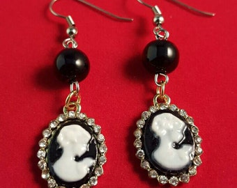 Dangle black and white cameo earrings embellished with rhinestones.