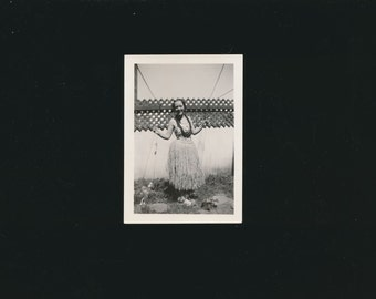 photo of a young lady in a grass hula skirt, 1940's.