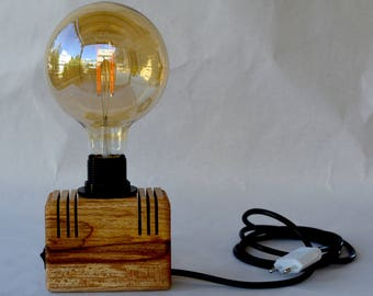 Wooden cube lamp with Edison bulb. Table wooden lamp with small black switch.
