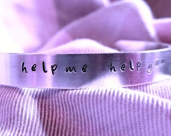 "Hand stamped cuff bracelet with ""help me help you""."