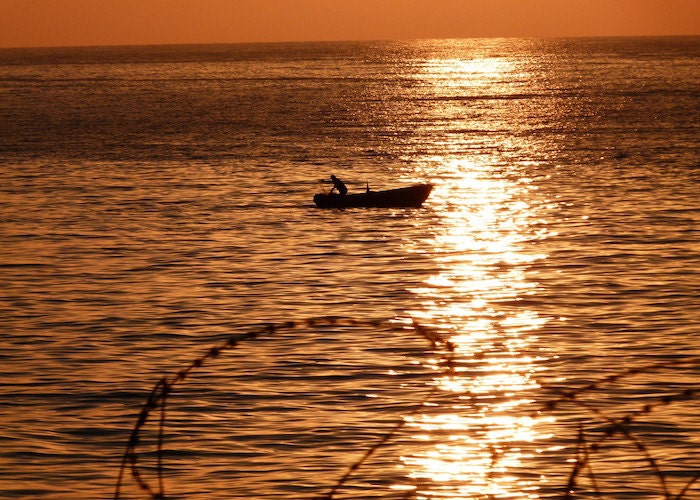 Sunset Sea View – Sunset Seascape Travel Photograph Featuring A Fishing Boat And Fisherman