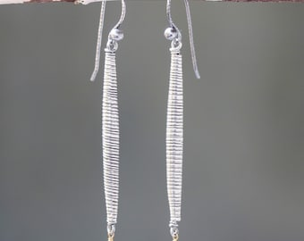 The sterling silver tube earrings in oxidized textures and ruby with hook style