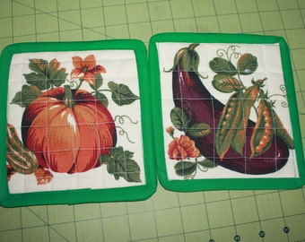 A pair of quilted potholder pumpkin and eggplant. reversible; insulated