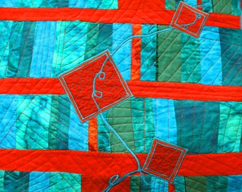 A quilted art wall hanging, modern geometric in red and teal