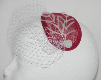 A Red teardrop fascinator on a hair comb with white chevron feathers and veiling