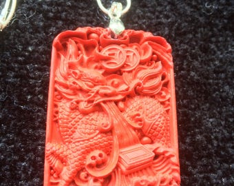 Red Chinese cinnabar sculptured ingot pendant on silver tone chain