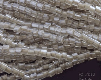 Vintage clear over taupe core hex cut seed bead. Size 10. 34 gram hank. B17-209(e)