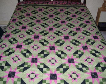 Bed size hand quilted quilt-in a cross hatch design and it is pink and green