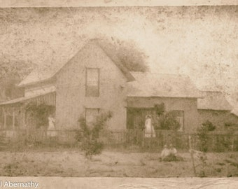 Photo from 1885 of a house with ladies on the porch and children playing in the yard