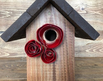 Outdoor birdhouse with red rose accents