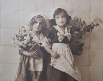 postcard with two girls with some flowers, vintage postcard