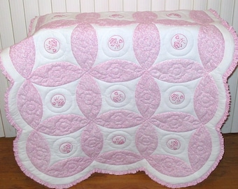 "Crib Size Quilt,  Pink floral fabric, Pattern ""Circles"" with a ruffle around outside of quilt"