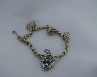 Sterling silver four charm bracelet with bluestone heart lock