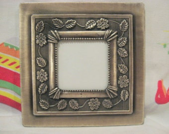 Small, silver metal photo, picture frame with glass,  raised flowers, vines and leaves