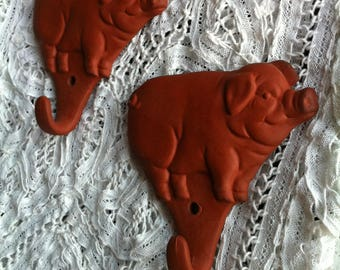 Two Terracotta Pig Shape Wall Mount Hooks With A Sticker That Reads Made In Japan