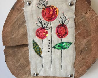 Free Motion Embroidery Flowers mounted on a tree slice