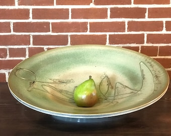 "Striking handmade 20"" porcelain charger with slip trailed design, traditional shino, matte green glaze and wood ash detail."