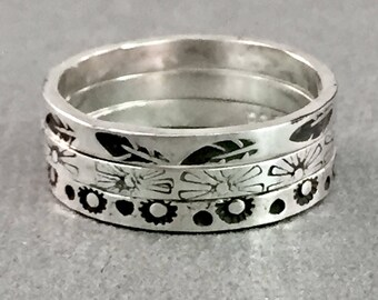 Size 5.5. Sterling silver stacking ring trio; one with leaves, one with daisies, one with dots and tiny flowers. SayLaVee