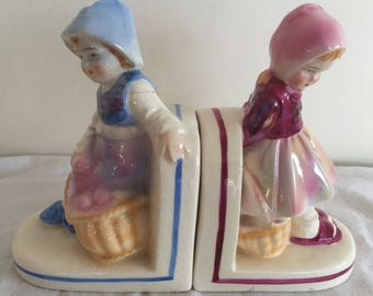 A pair of vintage ceramic bookends  in the form of children with lustre glaze.