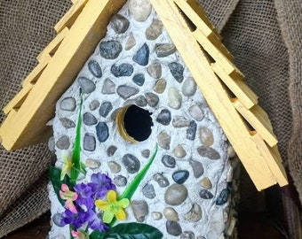 Stone birdhouse with yellow accent and flower accents. Easy clean out and a hanger. Affordable and handmade in Michigan.