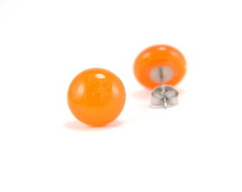 Orange glass stud earrings with clear top, on surgical steel earring posts