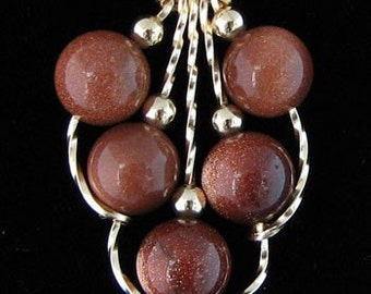 Lynda is a Goldstone pendant and 14kt rolled gold pendant