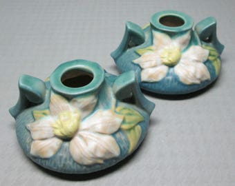 Roseville candle holder pair Clematis in blue , 1158-2 and have B and 3 written on them .